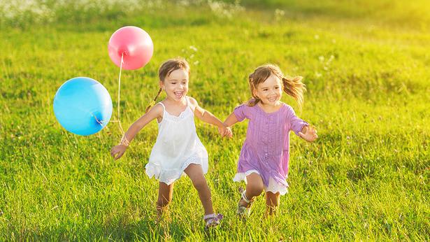 Dos niña corriendo en el césped, una lleva falda blanca, con dos globos, azul y rojo en la mano, otra lleva falda violeta