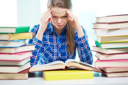 Retrato de niña tensa tocando la cabeza mientras lee el libro