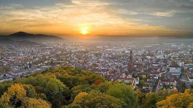 Por la mañana, el sol sale desde la distancia e ilumina la ciudad