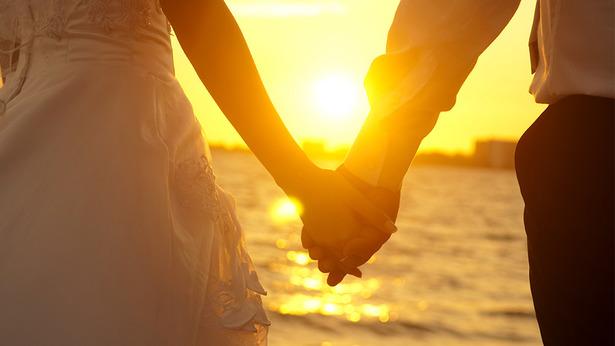 Una pareja, de cara al atardecer, tomados de la mano
