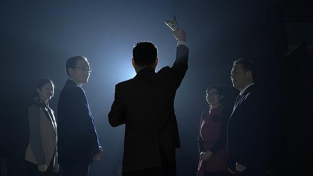 Una persona sosteniendo un trofeo, frente a la audiencia, emocionada, la persona a su lado arroja una mirada de envidia