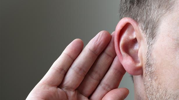 un hombre pone la mano al lado de la oreja escuchando algo. Tiene barba