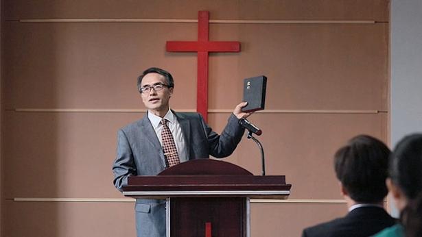 Un pastore tiene la Bibbia nella chiesa