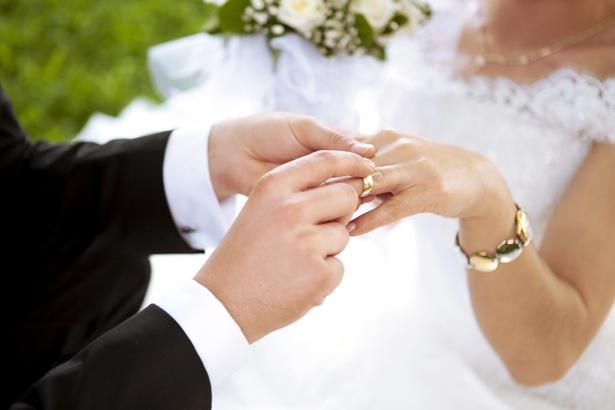 Giorno del matrimonio. Sposo mettendo un anello sul dito della sposa