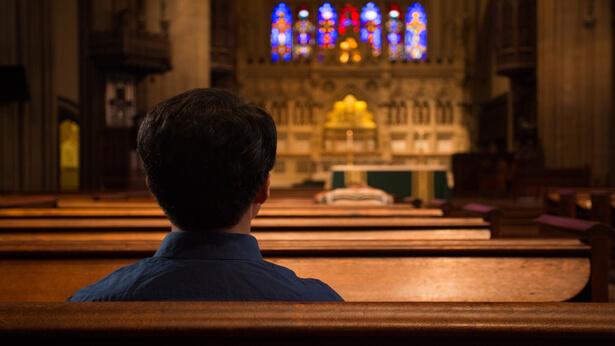 un cristiano sta pensando nella chiesa