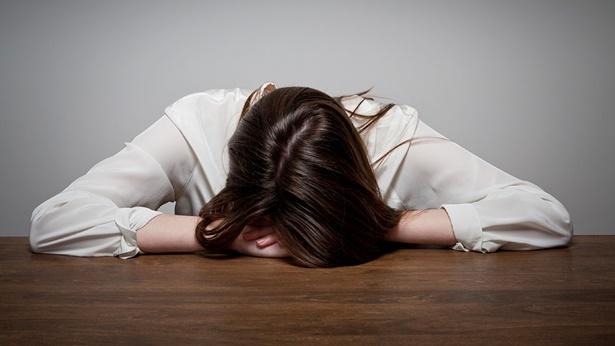 一個女生很沮喪的趴在桌子上