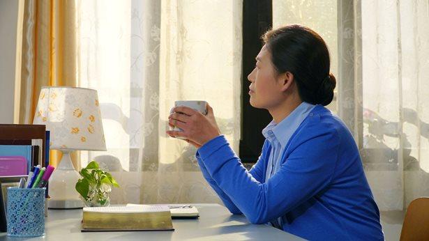 一個姊妹手捧水杯坐在窗前回想