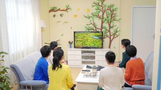 幾個弟兄姊妹在室內看福音視頻